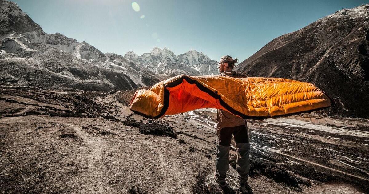 Mann mit Schlafsack beim Campen