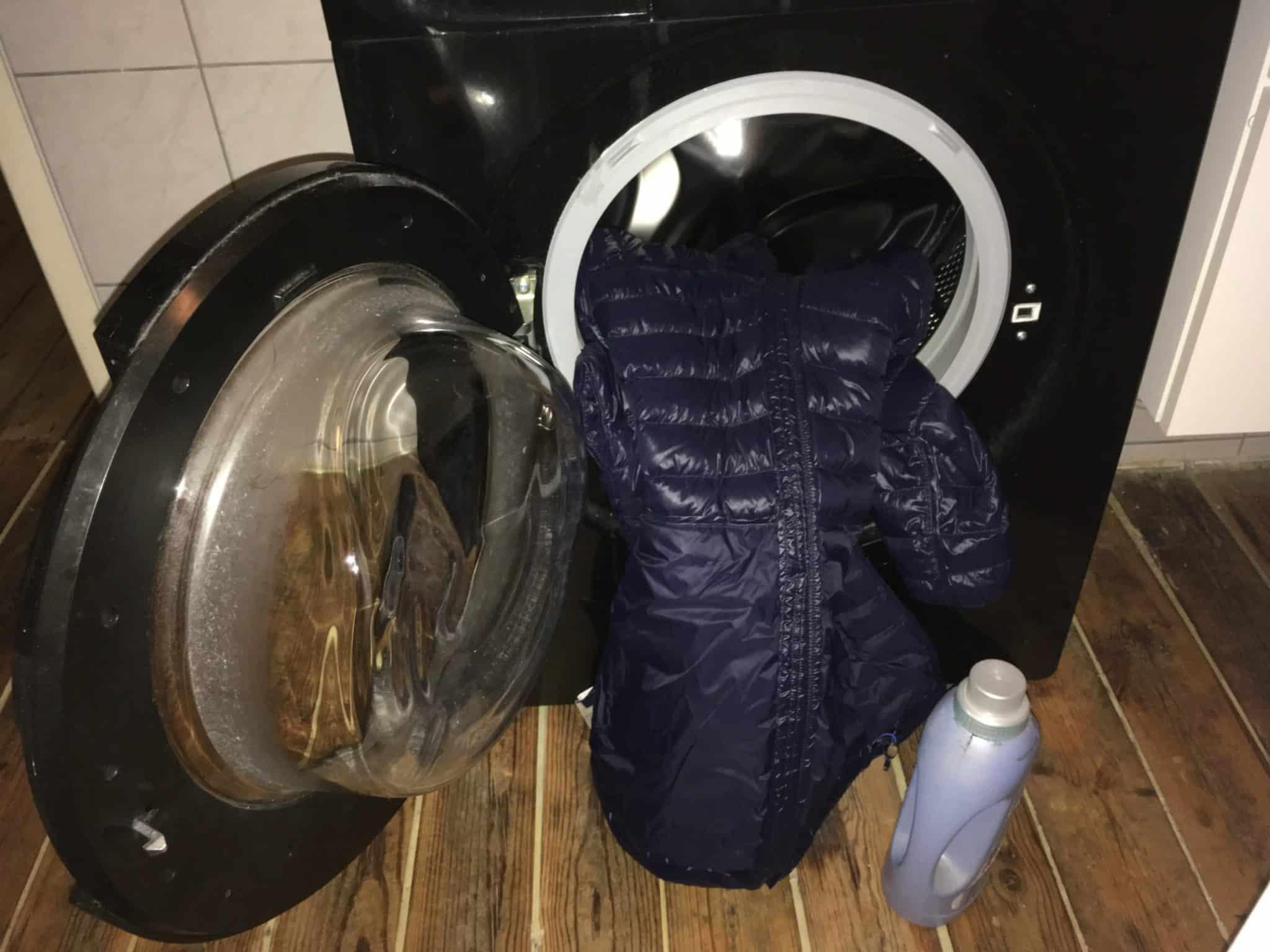 Daunenjacke und Waschmittel vorm Trockner