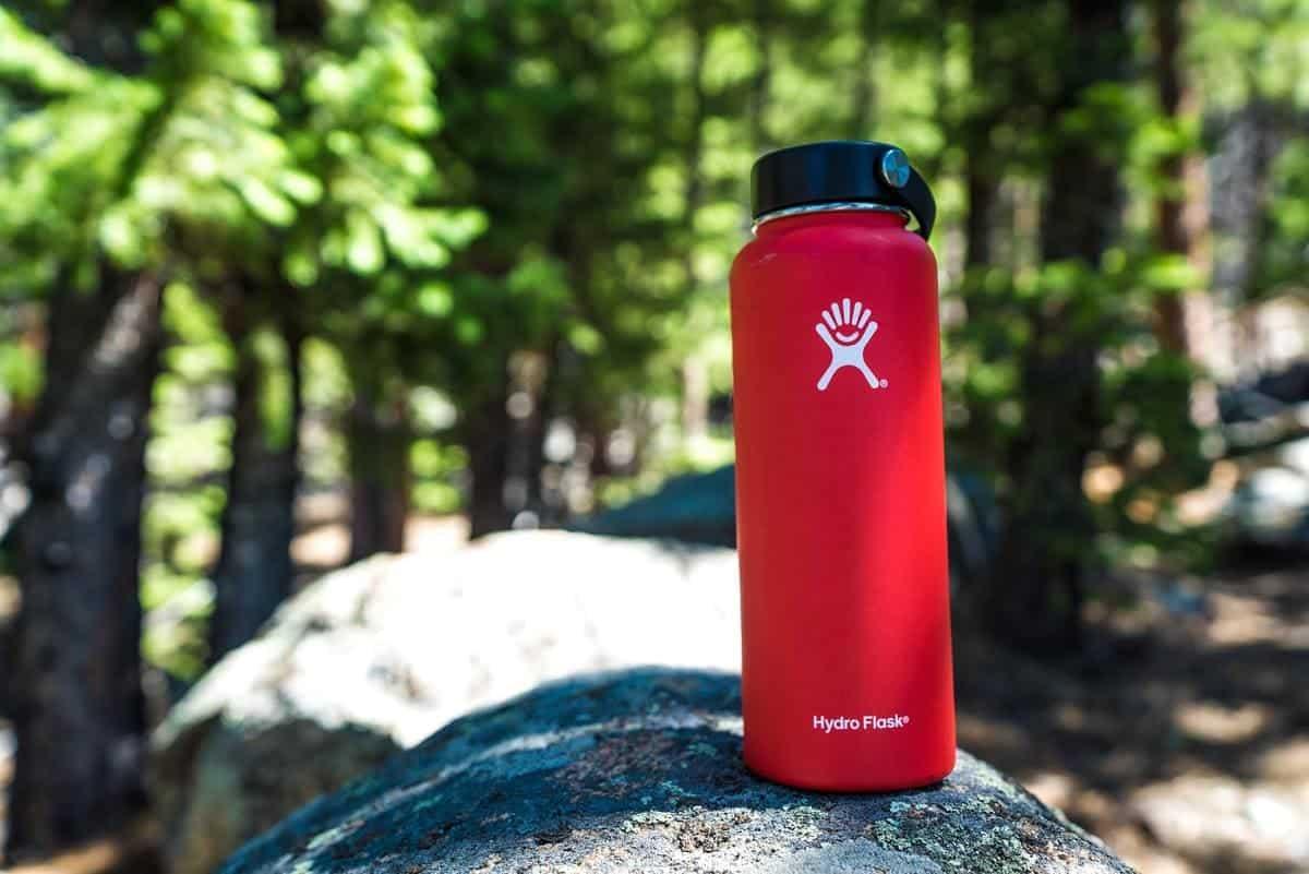 rote Edelstahl-Trinkflasche im Wald