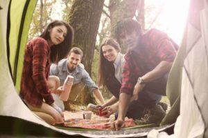 Ansicht auf Gruppe von Menschen im Wald aus einem Zelt